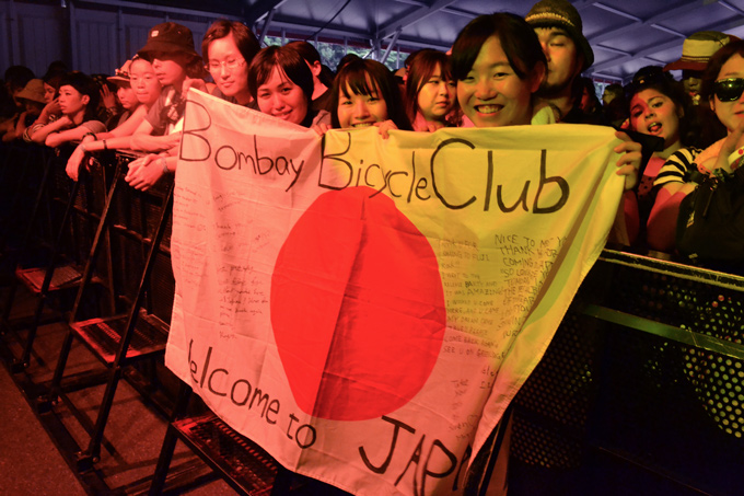fuji rock festival concertgoers holding bombay bicycle banner