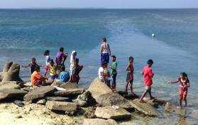kids on rock at ocean, Ebeye, Marshall Islands