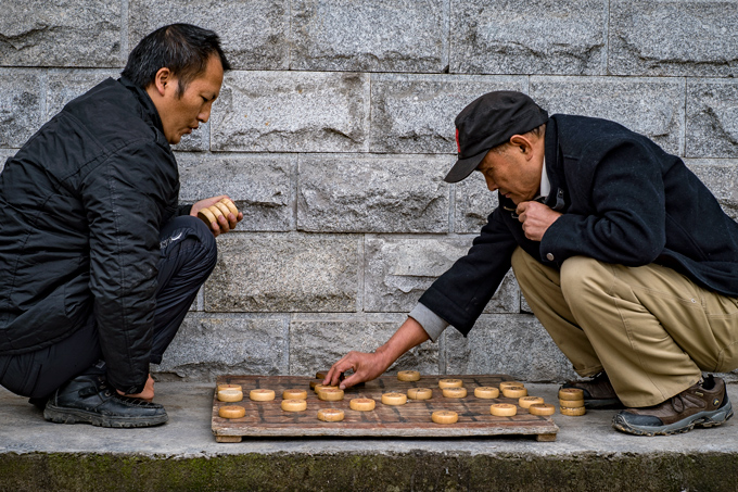 Men playing game on street in Zhangjiajie, China