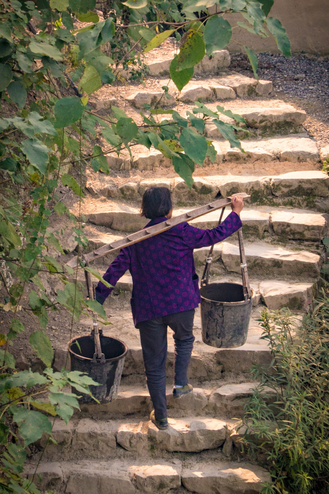 Woman carrying water buckets in Yangjiajie, China