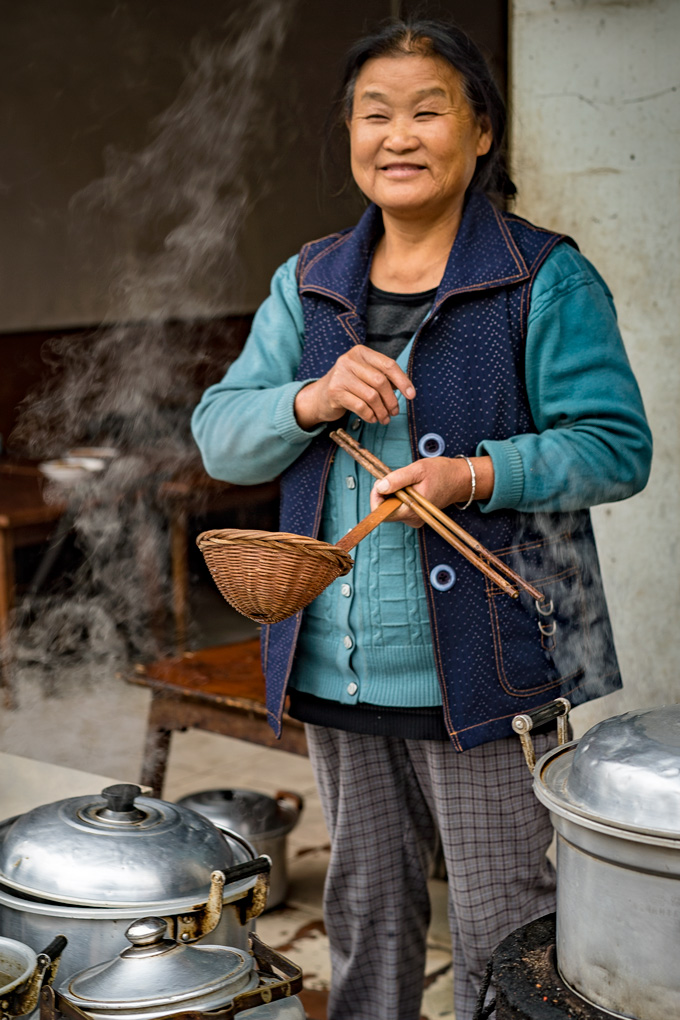 Woman cooking street food in Zhangjiajie, China
