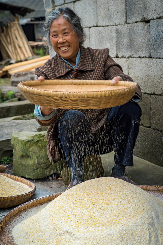 Woman sifting flour in Zhangjiajie, China