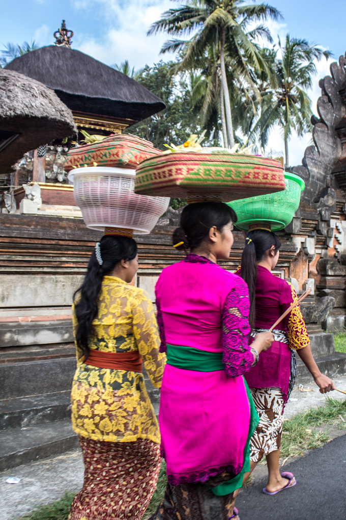 Balinese women carrying baskets on their heads, walking through Bali