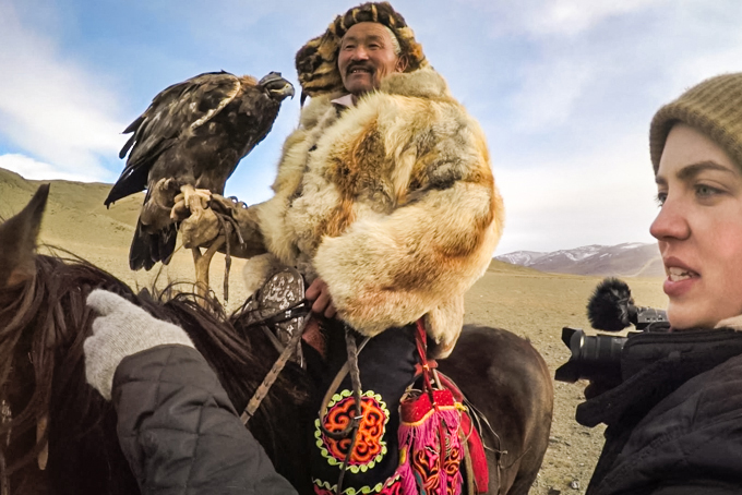 Ansley Sawyer directing, Mongolian man on a horse with a hawk in a traditional fur coat