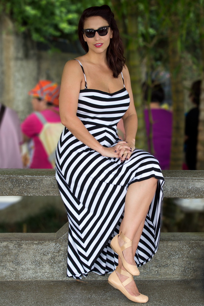 Jessica Peterson, woman in black and white striped dress, sitting at Victoria Peak, Hong Kong