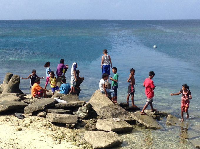 kids on rock at ocean, Ebeye, Marshall Islands