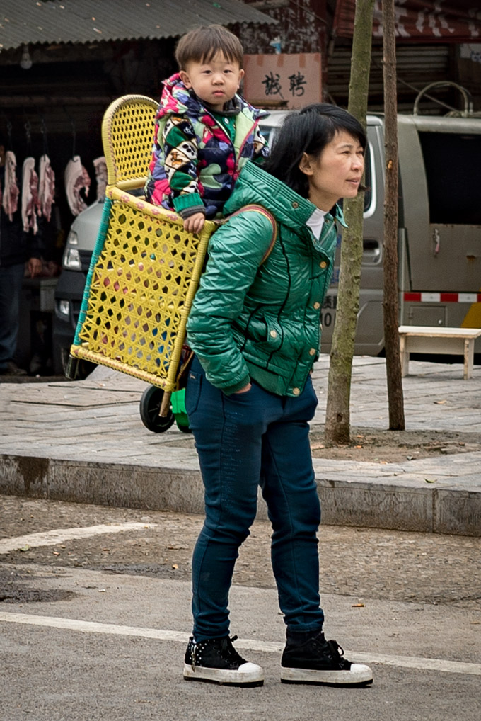 Mother carrying child on back in Zhangjiajie, China