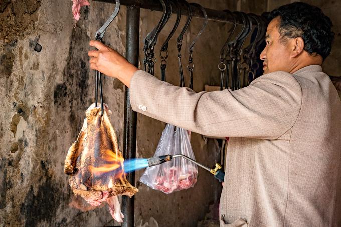 Butcher torching meat in Zhangjiajie, China