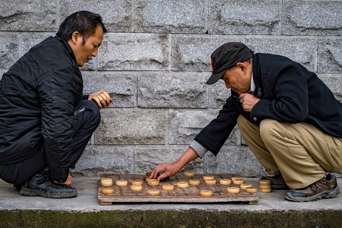 Men playing game on street in Zhangjiajie, China