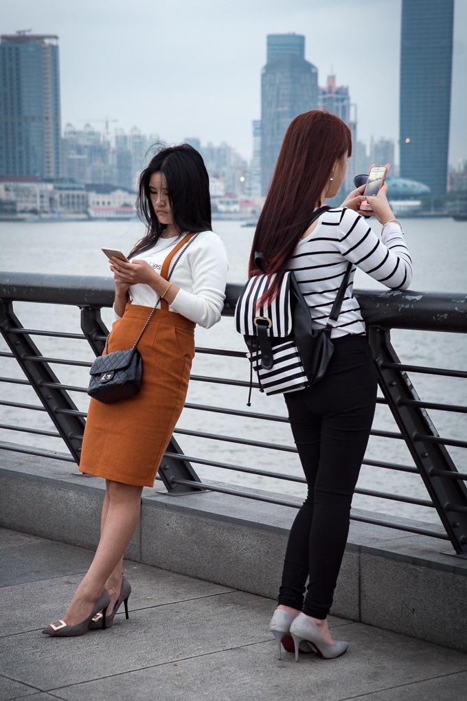 Women texting at The Bund, Shanghai, China
