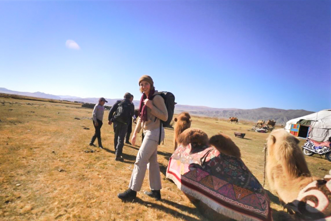 Ansley Sawyer walking in Mongolia with a camel at her side