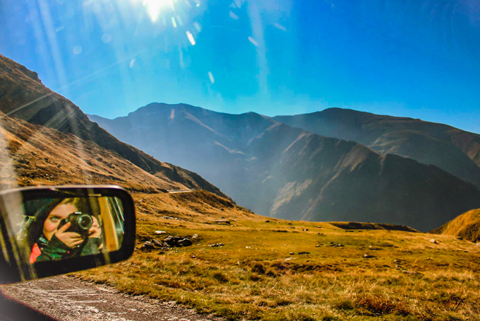 Ansley Sawyer reflected in a car mirror while driving through mountains in Mongolia
