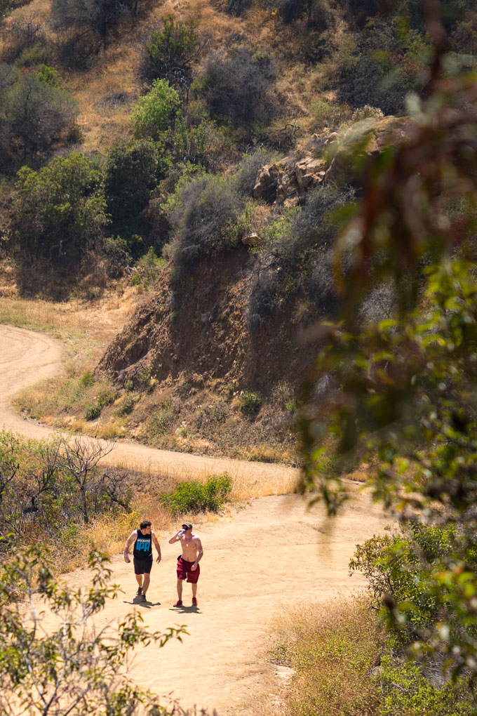 Two people walking the trails of Hollywood Hills below the Griffith Observatory, Los Angeles, California
