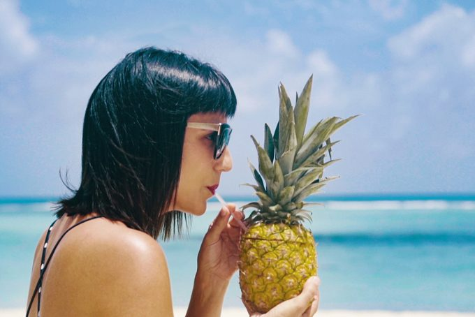 Jessica Peterson of Global Girl Travels sipping a pineapple on Saona Island, Dominican Republic for Barcelo Hotels, barcelostories.com