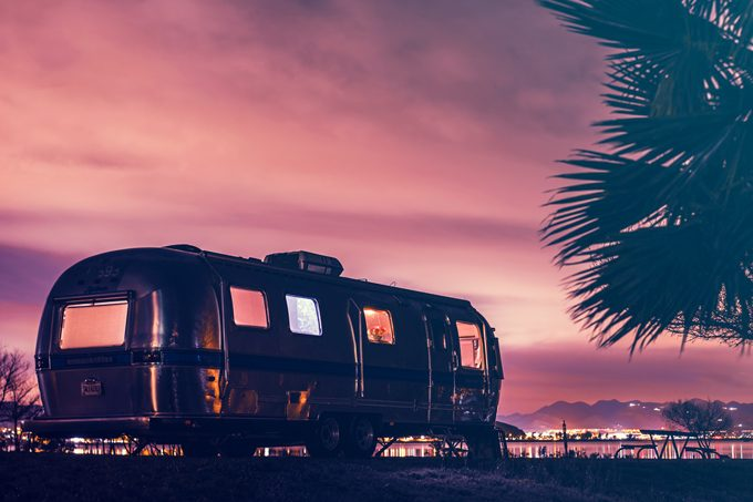 Global Girl Travels Airstream parked on a lake in California at sunset
