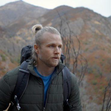 Man hiking in mountains wearing WantDo jacket